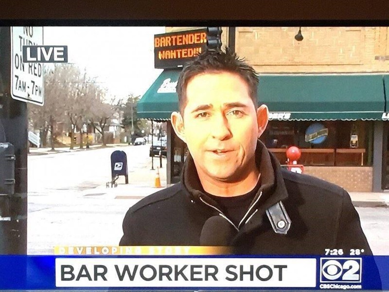 Funny image of news reporter in front aof a bar where a bar worker was shot, sign in background says BARTENDER WANTED, too soon perhaps?