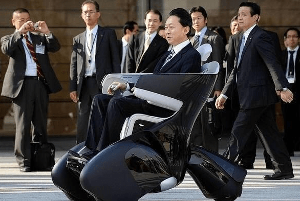 Japanese man in suit riding around in wheelchair that looks super futuristic.
