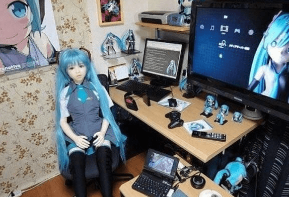 Blue-haired anime figure sits at desk full of products devoted to her.