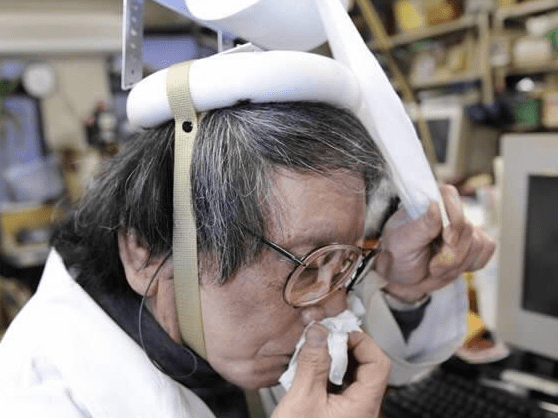 Old woman blows her nose using weird headset made out of kleenex.