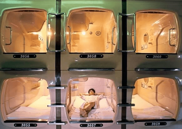 Guy sleeps in weird cubicle sleeping chamber that looks like it's part of a futuristic prison.