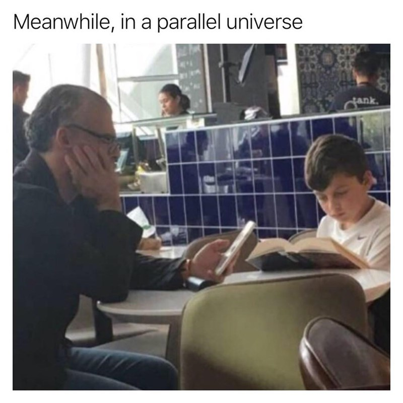 Funny meme regarding a parallel universe in which an old man is staring at his phone while a young boy reads a long book.