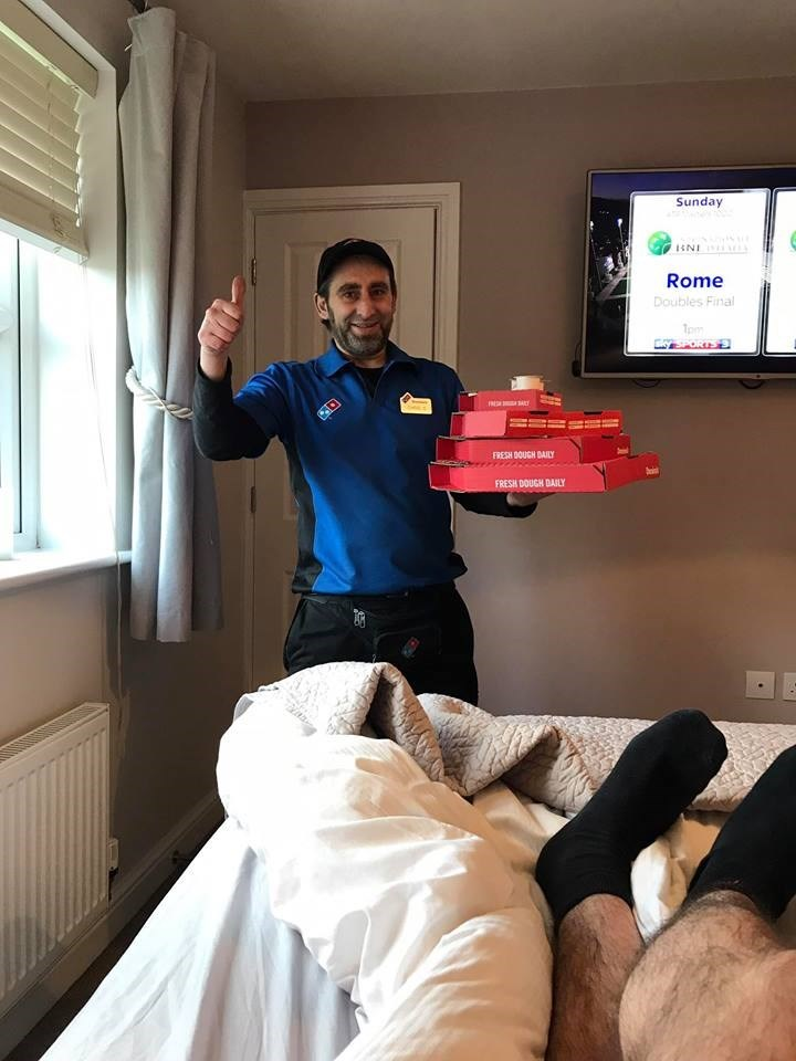 The Domino's pizza man arrives at this bedroom, with a stack of fresh pizzas.
