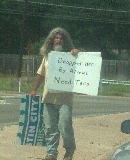 "Funny picture of a man standing on the side of the road (he looks homeless) with a sign that says ""dropped off by aliens, need taco."""