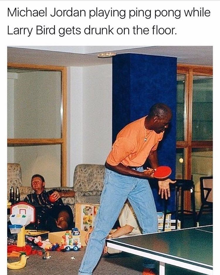 Michael Jordan playing ping pong in orange shirt and blue jeans as Larry Birds is getting drunk on the floor.
