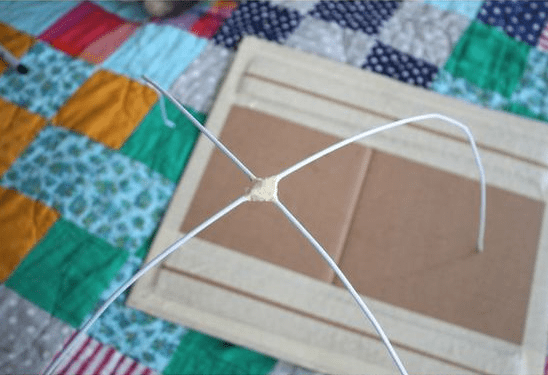 With some tape and resourcefulness, the wires from the hanger are starting to make the wire-frame for the tent.