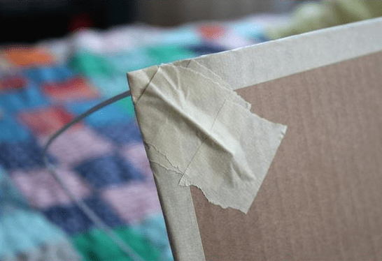 Close up, showing how to secure the corners of the tent to the cardboard.