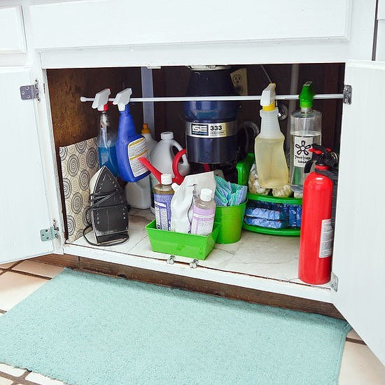 Use a rod to organize spray bottles under the sink