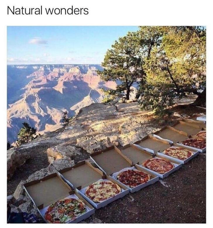 Pic of a row of different pizzas in front of a beautiful nature landscape