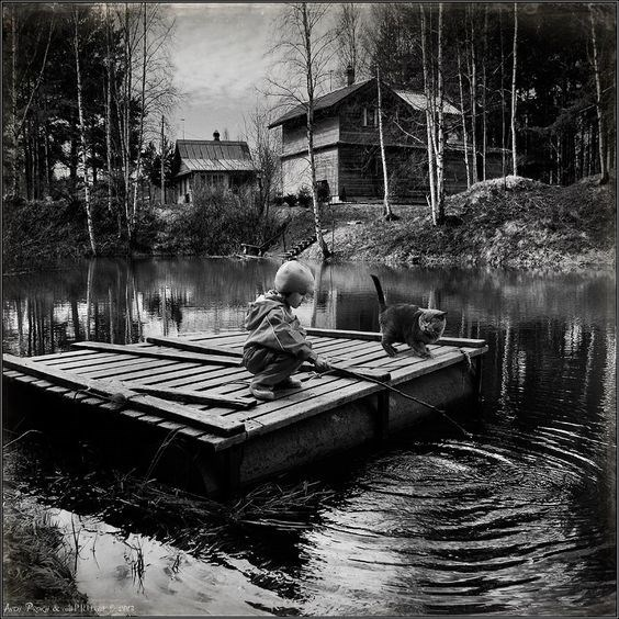 Andy Prokh photo of boy playing on a raft in the water with a cat on board.
