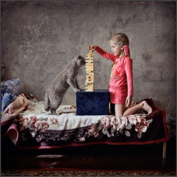 colorized Andy Prokh photo of girl and cat playing Jenga