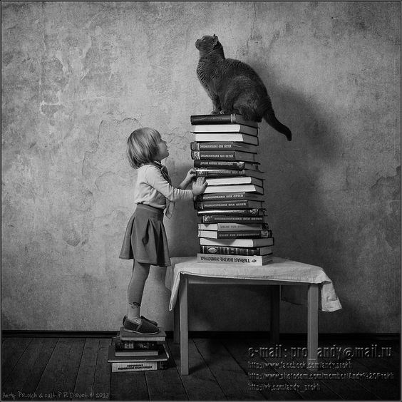 Andy Prokh black and white of a girl and cat standing on top of stacks of books.