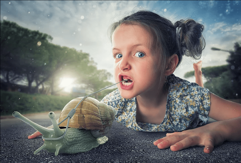 John Wilhel photographs his daughter with a comical snail in a fantasy like photo
