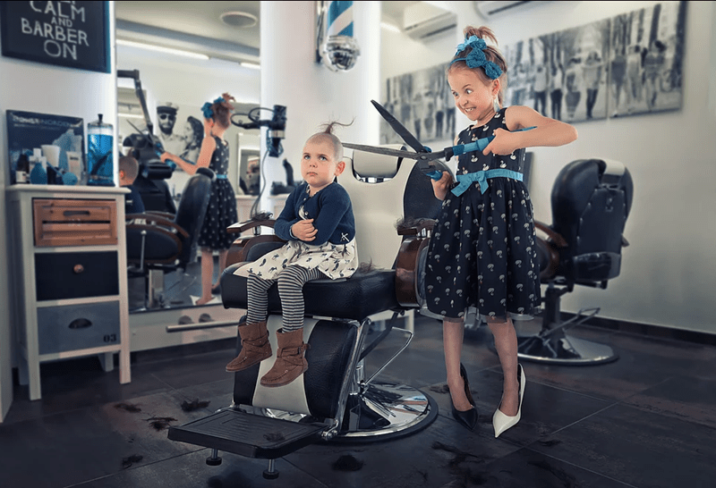 John Wilhel photo of his daughter using gardening sheers to give each other haircuts.