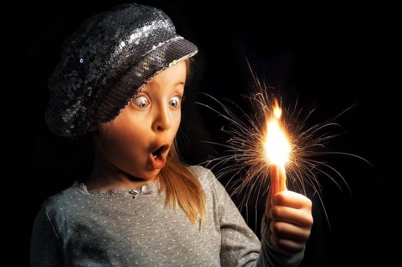 Girl holding burning candle by John Wilhel
