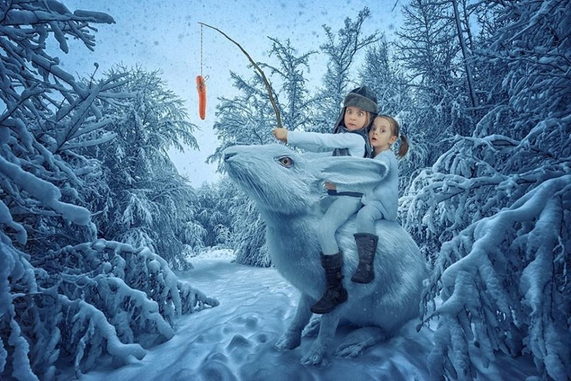 Funny picture by John Wilhel of his daughters riding a giant rabbit and luring it with a carrot led by a string.