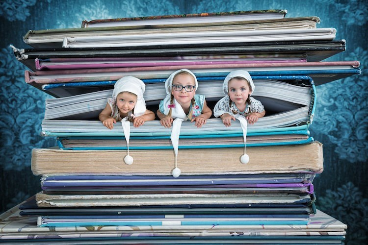 Photoshoped work of art by John Wilhel of his three daughters taking a nap in massive oversized books.