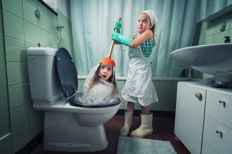 John Wilhel's daughters plunging the toilet as one is stuck in it.