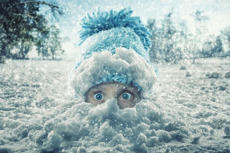 Girl over her nose in snow in Switzerland by John Wilhel