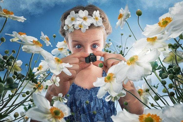 Girl in spring holding tiny camera in field of white flowers by John Wilhel