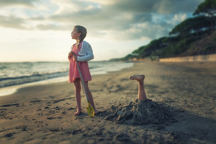 John Wilhel daughter stares at the sea as her sister is stuck in the sand head down.