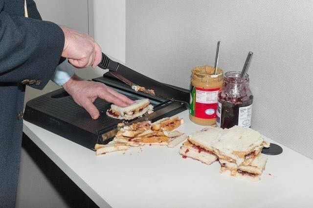 Office worker using a paper guillotine to slice up a peanut butter and jelly sandwich.
