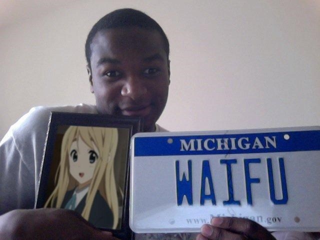 Man holding a vanity plate from Michigan with the letters WAIFU
