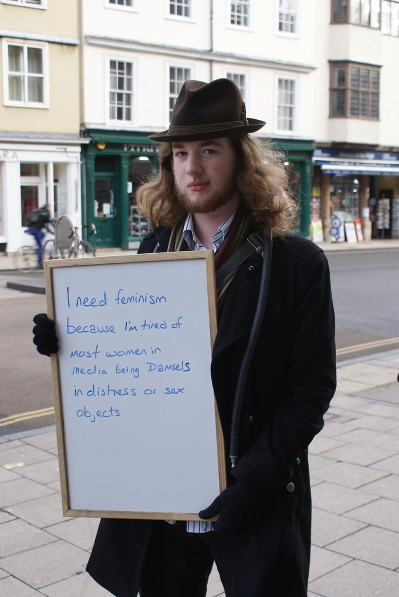 Cringeworthy dude holding white board with statement about why he needs feminism.