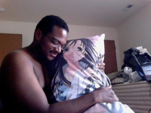 Black man hugging his pillow that looks like an anime woman.