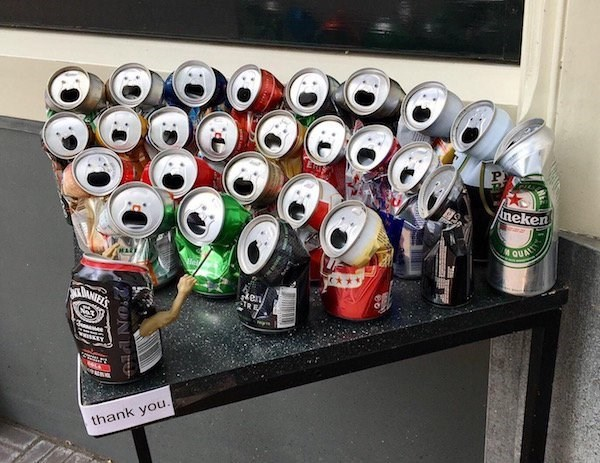 Funny picture of cans of soda bent to look at one can giving a speech.
