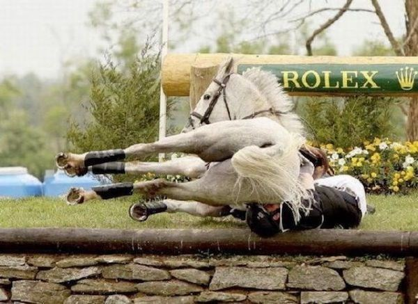 Horse with ROLEX sign behind him as he fails to clear the hurdle and crushes the rider in the process.
