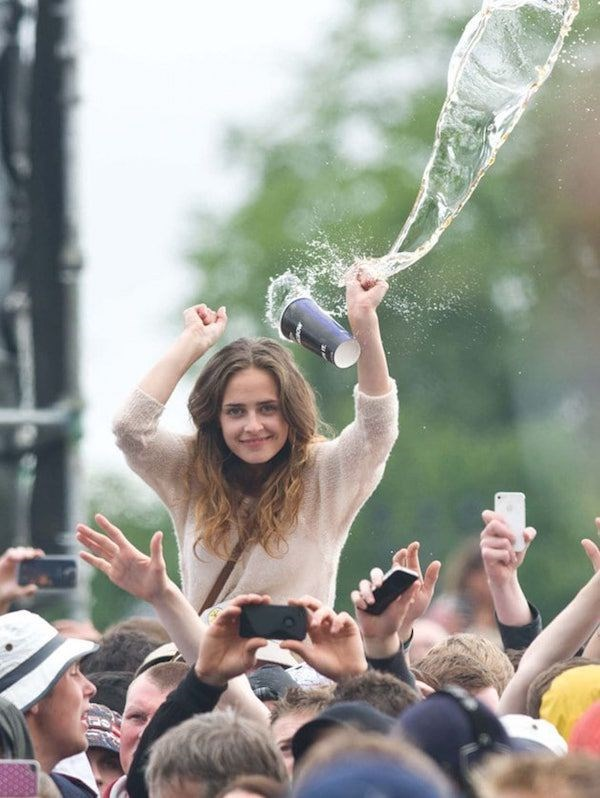 Girl in the crowd on someone's shoulders as a cup of water flies by