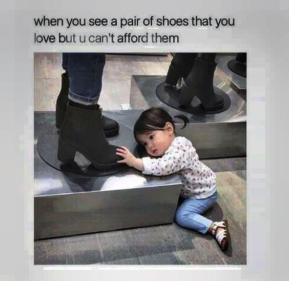Little girl admiring shoes on a mannequin