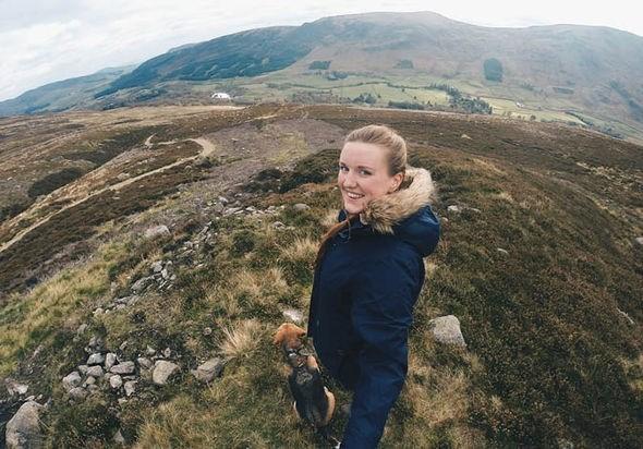 Emma Higgins walking a dog through a beautiful field.