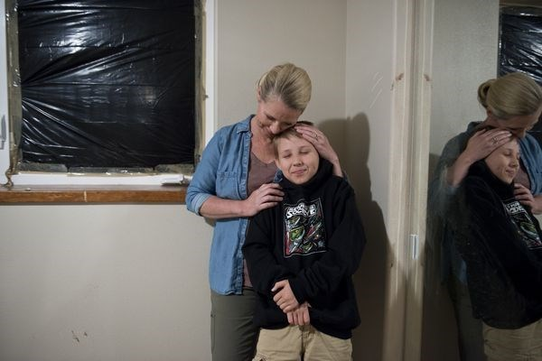 Zach Landis and his mom in the room next to the broken window which the bear used to gain entry to the boy's room.