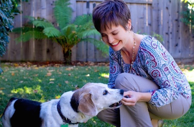 picture of smiling woman feeding a dog in a backyard outdoors setting