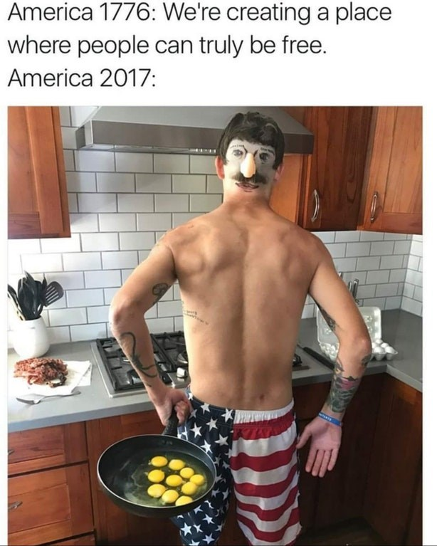 Meme about how far we've come as free Americans, photo of a man in an American flag swimsuit with a fake face on the back of his head while making breakfast.