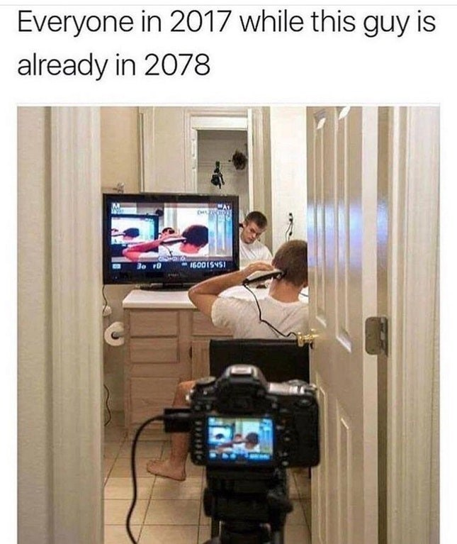 Funny future meme about someone being in 2078 - kid using a camera hooked up to his TV to buzz the back of his head.