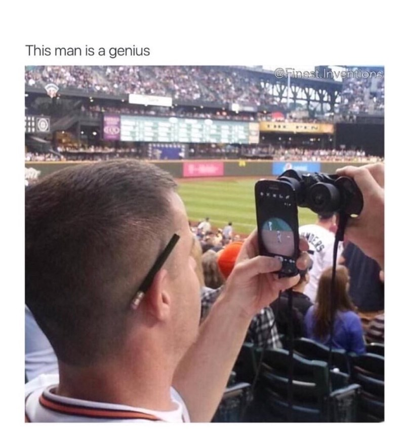 Man at a baseball game with his phone up to his binoculars to get a real close up view of the game.