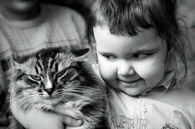 Kid giving the side eye to a cat who is not ammused.