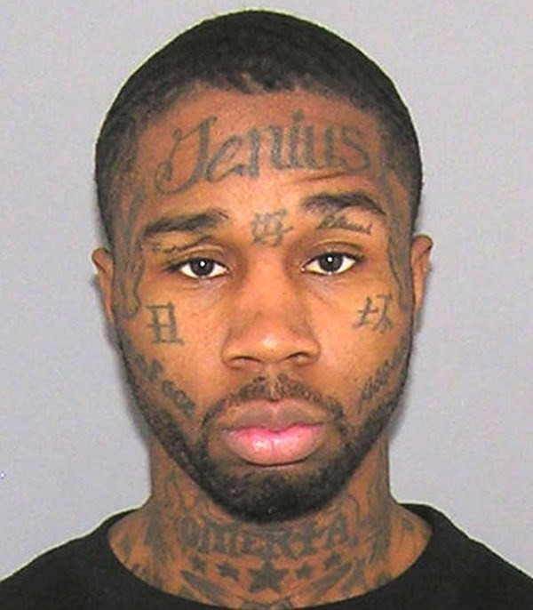 Black dude with faded tattoos on his face.