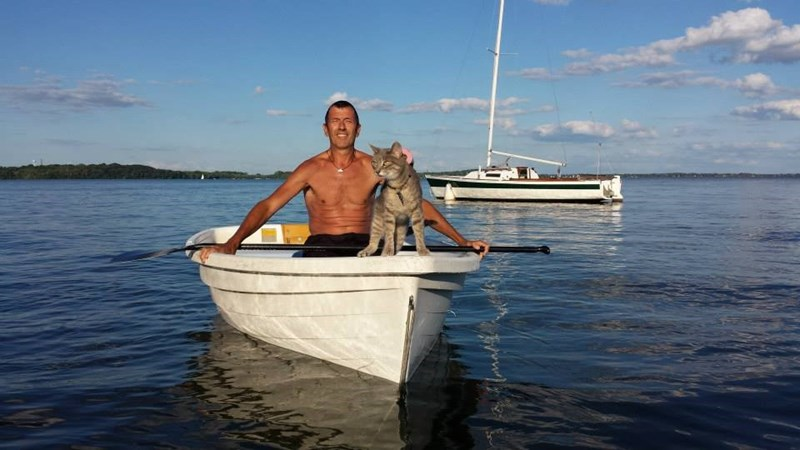 Dr. Kenneth Lambrecht in a small boat with his cat, Little Bug
