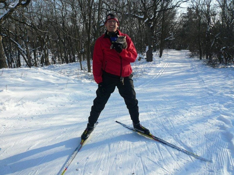 Dr. Kenneth Lambrecht on Skis and holding his cat Little Bug as the about to go downhill.