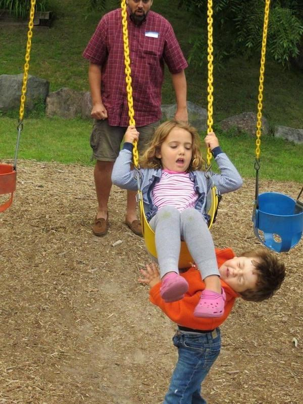 perfect timing photo of kid getting kicked in the face by his sister on the swing