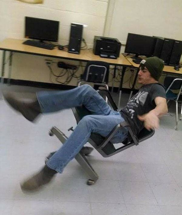Perfect timing photo of greaseball dude in an office chair leaning back just as he is falling over