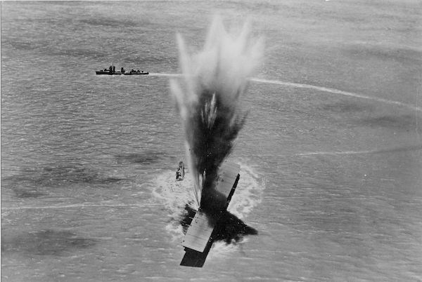 Black and white photo of a large boat getting a direct hit, with perfect timing as it absorbs the blast.