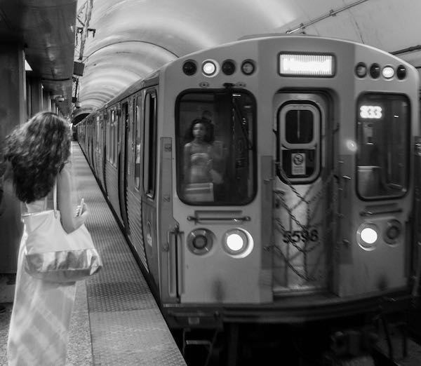 Perfect timing black and white photo of NYC subway in which woman's reflection looks like she is a ghost on the passing train.