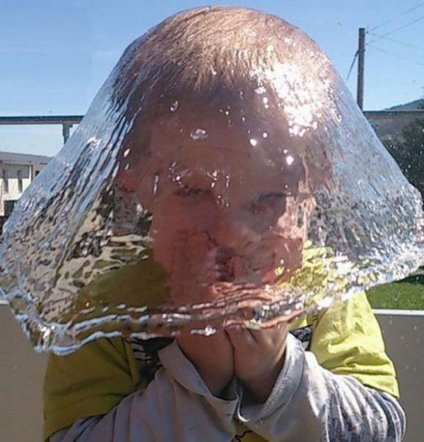 perfect timing photo of water splashing on a kids head.