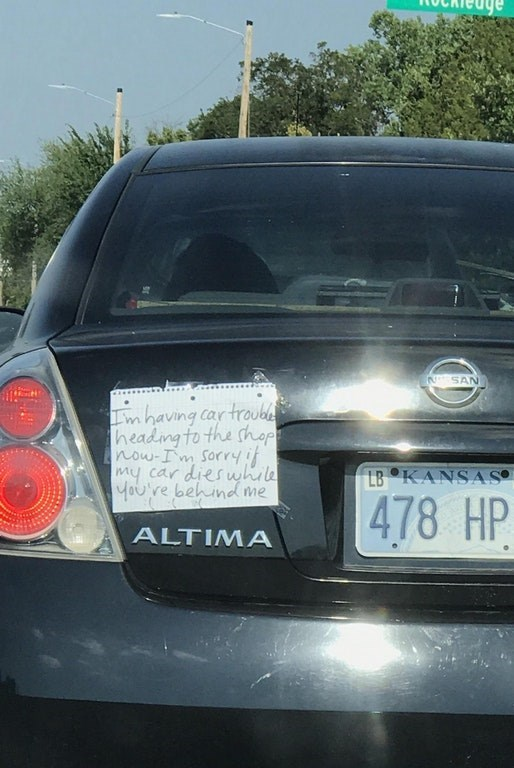 Picture of car's bumper sticker that has handwritten note about how car might break down.