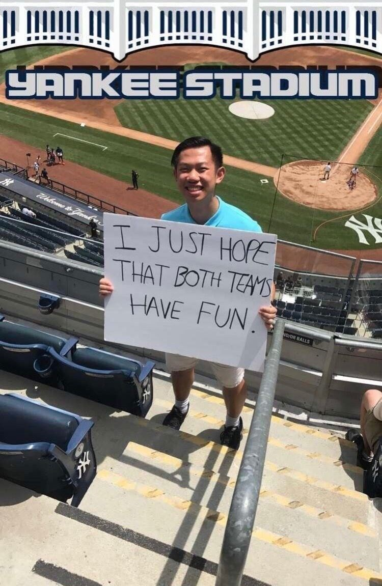 Chinese tourist at Yankee Stadium holding a sign saying he just hopes both teams have fun
